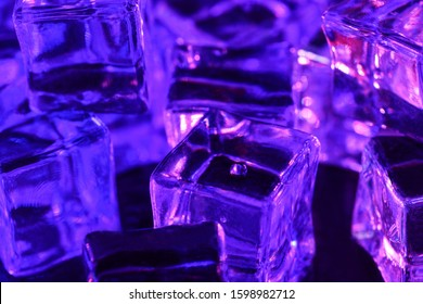Ice cube. Close-up of ice cubes with  pink and purple backlight  thawn. Macro horizontal photography