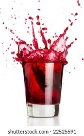 Ice cube dropped into a glass of grape juice