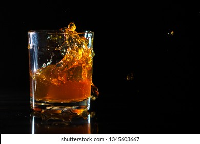 Ice cube falls into a glass with whiskey on black background. Fluid in motion. Droplets of spray.