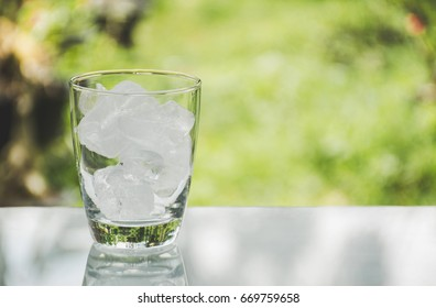 Ice cube in the glass on table with nature background