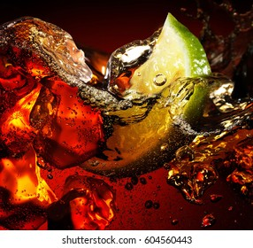 Ice cube and lime splashing cola glass, closeup, black background