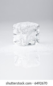 ice cube on neutral background with reflection