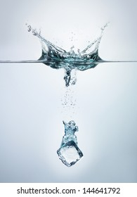 Ice cube splashing into clear water surface view