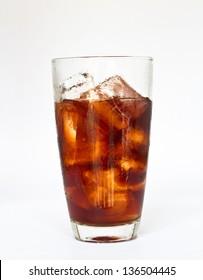 ice cube splashing into glass of coke white background.