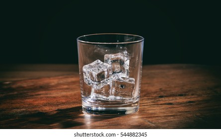 Ice cubes in an empty glass on a wooden bar counter, dark background, front view with details