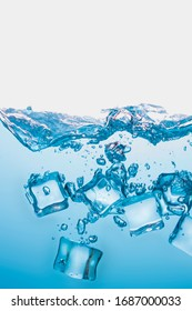 Ice cubes falling into the blue water create beautiful bubbles.