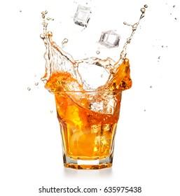 ice cubes falling into a splashing orange cocktail isolated on white