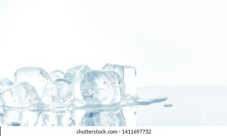 Ice cubes heap on reflective mirror surface background. Isolated on white.