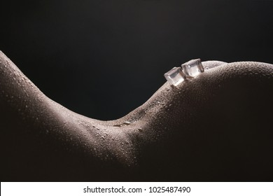 Ice cubes lying on woman body cropped shot