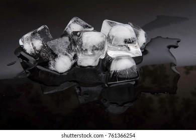 ice cubes melting on dark background