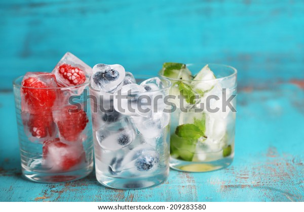 Ice cubes with mint leaves, raspberry and blueberry in glasses, on color wooden background