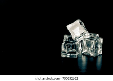Ice cubes on black background. Selective focus. Toned.