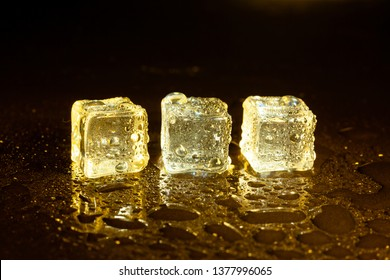 ice cubes on a reflections yellow light.