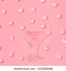 Ice cubes pattern with martini glass on pastel pink background. Minimal summer drink concept. Flat lay.