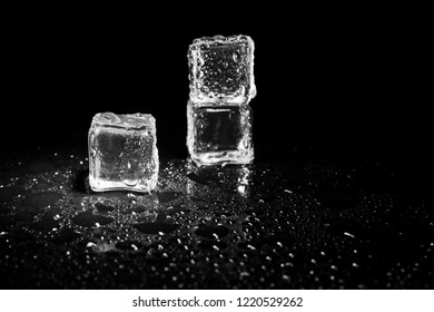 ice cubes reflection on black table background.
