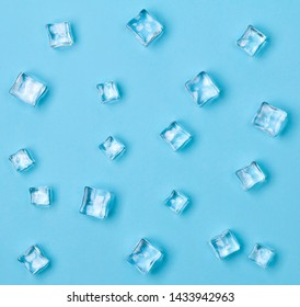 Ice cubes scattered on a light blue background. Flat lay, top view