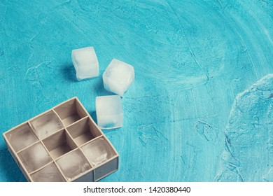 Ice cubes and silicone mold on a blue stone background. Ice production concept. Flat lay, top view