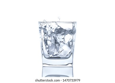 ice cubes splash into glass of water