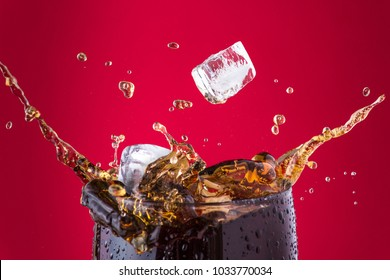Ice cubes splashing into cola drink