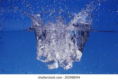 Ice cubes splashing into water, close-up