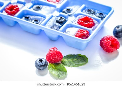 Ice cubes with ice tray and berries with mint on white table bac