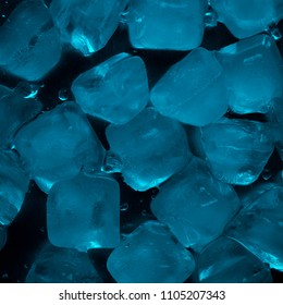 Ice cubes in turquoise color on a black background top view