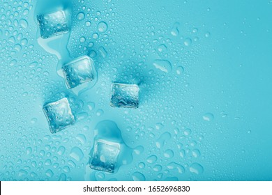 Ice cubes with water drops scattered on a blue background, top view.