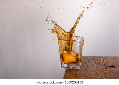 ice falls into a glass standing on the edge with whiskey and splashing on a gray background