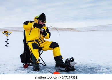 Ice fisherman with a fish on his line.