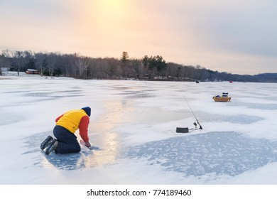 ice fisherman with a fresh catch on a frozen lake at sunset