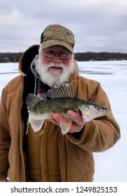Ice fisherman holding a Walleye while standing on a frozen lake