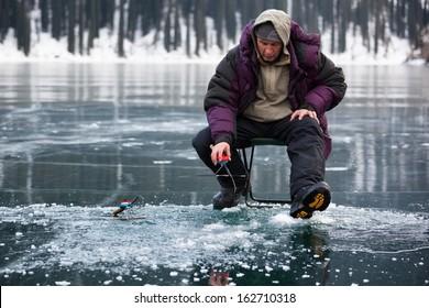Ice fisherman on winter mountain lake