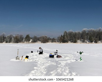 Ice fishing on a frosty morning with snow covered trees in the background