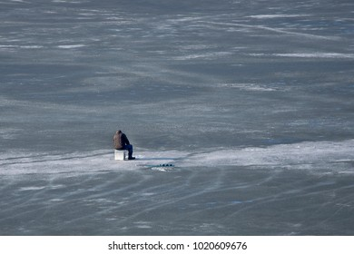 Ice fishing on river. Fisherman on frozen lake or other reservoir.