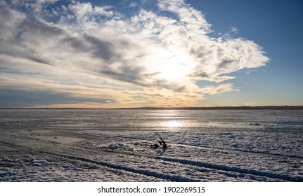 An ice fishing rod sit on top of the frozen McGregor Lake under a dramatic sky in Vulcan County Alberta Canada.