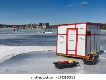 Ice fishing shack with sleds and fishermen drilling hole on frozen Kempenfelt Bay of Lake Simcoe at Barrie Canada