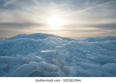 Ice floe against the frozen sea, cloudy sky and sun on background
