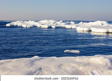 Ice floes on the water surface, sea landscape. Clear sunny day, cold season. The cloudless blue sky, deserted.