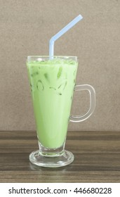 Ice green tea with milk on wooden table