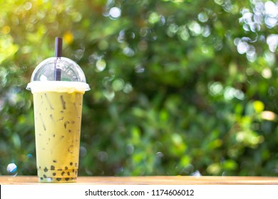Ice green tea with milk-tea  bubble on the wood table and green Bokeh tree background