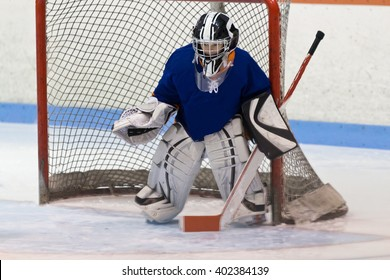 Ice hockey child goalie in net ready for the puck during a game