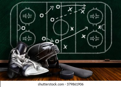 Ice hockey equipment consisting of skates, helmet, stick and puck with background play strategy drawn on chalk board.