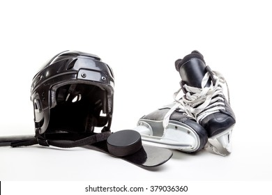 Ice hockey equipment featuring safety helmet, pair of skates and a hockey puck sitting on the blade of a hockey stick. Isolated on white background.