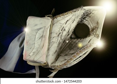 Ice hockey goalie catcher and puck under light.Hockey goalie catcher with black puck  under shining light.