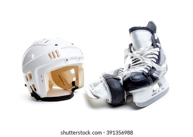 Ice hockey helmet and a pair of ice skates isolated on white background.