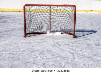 An ice hockey net torn from use sits on a rink in rural Ontario Canada.