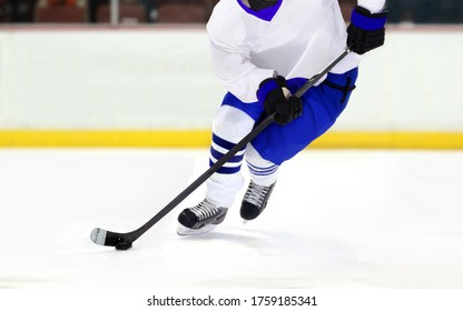 Ice hockey player on rink dribbling puck