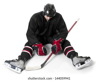 Ice hockey player sitting on ice with disappointment