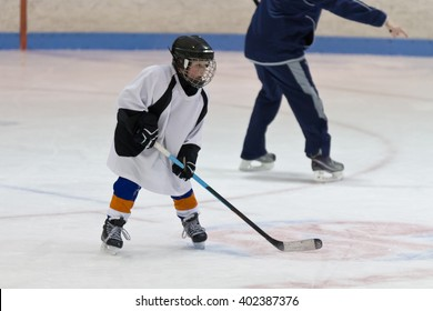 Ice hockey practice with player and coach during a drill