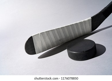 Ice hockey puck and hockey stick on isolated white background, copy space.